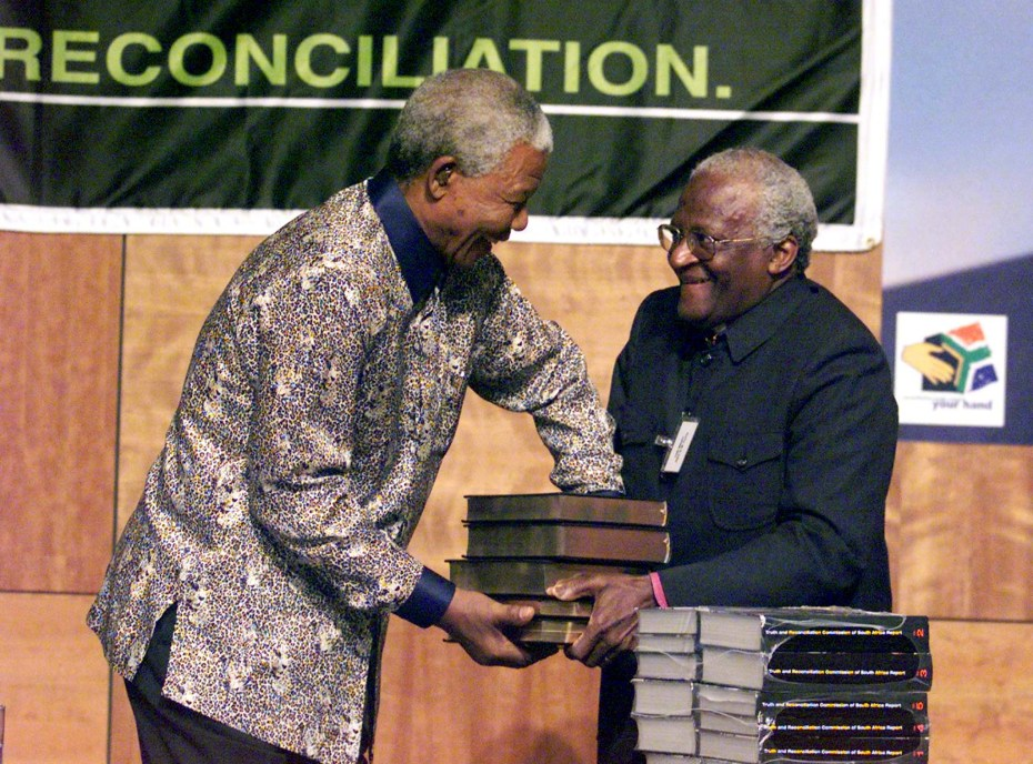 Chairman of the TRC (Truth and Reconciliation Commission) Archbishop Desmond Tutu (R) hands over the..